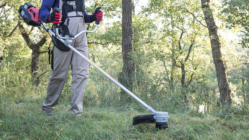 Front-three quarter view of Honda cordless brushcutter with model in a field.