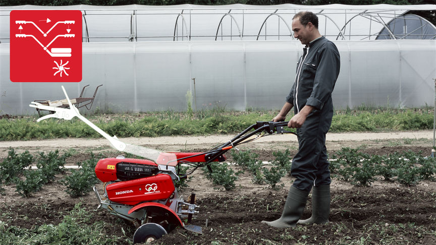 Versatile tiller, focusing on reversible handle, being used by model, garden location.