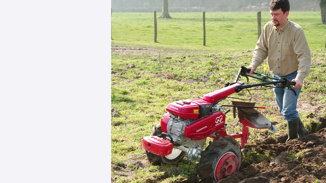 Versatile tiller with plough attachment, being used by model, garden location.