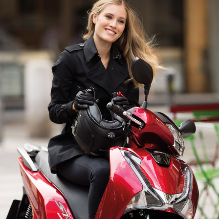 Donne sorridenti sedute sullo scooter
